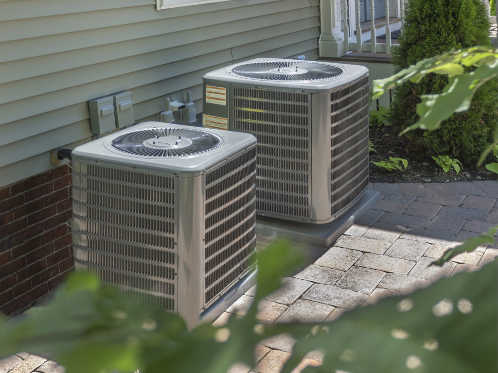 Two air conditioners on the side of a home sitting on stone patio